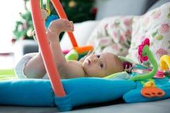 Bebê pequeno, jogando com brinquedos coloridos em casa imagens de stock