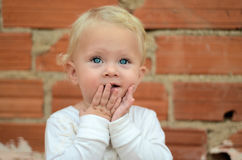 Bebê pequeno louro que olha com prazer fotos de stock