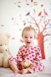 Bebê pequeno na cama que desgasta p?jamas vermelhos Fotos de Stock