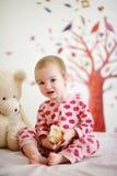 Bebê pequeno na cama que desgasta pyjamas vermelhos Imagens de Stock Royalty Free