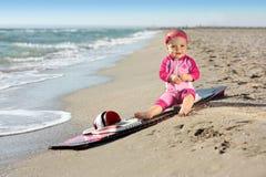 Bebê pequeno na praia da areia com placa de ressaca Fotos de Stock