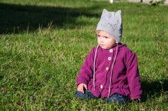 Bebê pequeno nas calças de brim revestimento e chapéu que fazem a aprendizagem andar suas primeiras etapas no gramado na grama ve Foto de Stock