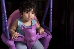 Bebê pequeno no balanço do unicórnio, equipado em casa imagem de stock