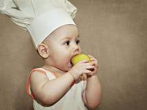 Bebê pequeno no chapéu de um cozinheiro chefe que come uma pera Fotografia de Stock Royalty Free
