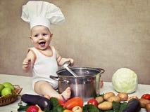 Bebê pequeno no chapéu e na concha de um cozinheiro chefe à disposição Foto de Stock