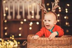Bebê pequeno nos chifres da rena que sentam-se em uma cesta de vime fotografia de stock royalty free