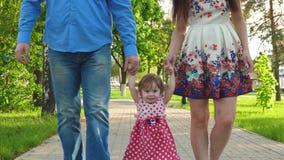 Bebê pequeno que aprende como andar com mamã e paizinho, família feliz que anda no parque do verão foto de stock