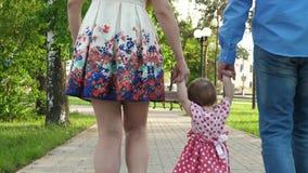 Bebê pequeno que aprende como andar com mamã e paizinho, família feliz que anda no parque do verão imagem de stock