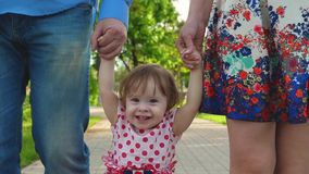 Bebê pequeno que aprende como andar com mamã e paizinho, família feliz que anda no parque do verão fotos de stock royalty free