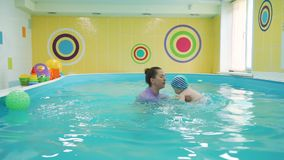 Bebê pequeno que aprende nadar na associação vídeos de arquivo