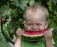 Bebê pequeno que come a melancia no jardim Imagem de Stock Royalty Free