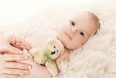 Bebê pequeno que encontra-se na cama com urso de peluche Fotografia de Stock Royalty Free