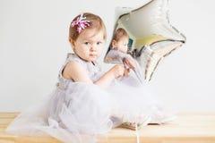 Bebê pequeno que guarda o balão estrela-dado forma prata Imagens de Stock
