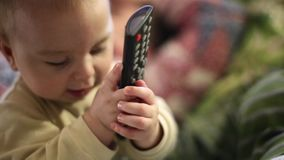 Bebê pequeno que joga com controlo a distância em casa Close-up filme