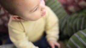 Bebê pequeno que joga com controlo a distância em casa Olhando a câmera filme