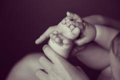 Bebê pequeno que joga com pés Imagem de Stock