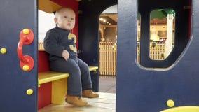 Bebê pequeno que joga em uma casa pequena no campo de jogos filme