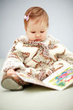 Bebê pequeno que lê um livro Imagens de Stock