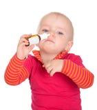 Bebé pequeno que pulveriza-se pulverizador de nariz no branco Imagens de Stock Royalty Free