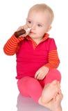 Bebé pequeno que pulveriza-se pulverizador de nariz no branco Fotos de Stock