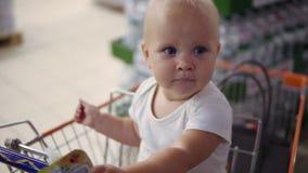 Bebê pequeno que senta-se em um carro do mantimento em um supermercado, esperando seus pais para fazer a compra Compra da família vídeos de arquivo