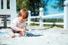 Bebê pequeno que senta-se na areia Foto de Stock Royalty Free