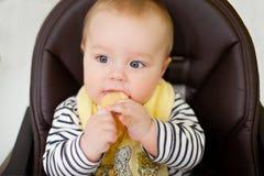 Bebê pequeno que senta-se na cadeira para alimentar e comer o biscoito especial para bebês Cozinha Fotografia de Stock