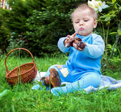 Bebê pequeno que senta-se na grama no parque e que olha estudado no cogumelo Imagens de Stock Royalty Free