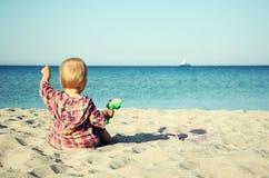 Bebê pequeno que senta-se na praia e que aponta no navio no mar Imagens de Stock Royalty Free