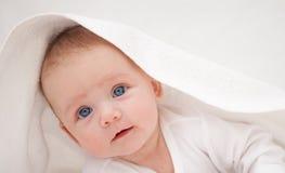 Bebê pequeno sob uma toalha branca que olha a câmera Imagens de Stock Royalty Free