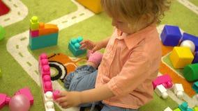 Bebê pré-escolar que joga com multi blocos de apartamentos coloridos no jardim de infância Desenvolvimento infantil no infantário filme