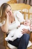 Bebê preocupado da terra arrendada da matriz no berçário