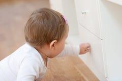 Bebê que abre uma gaveta Fotografia de Stock Royalty Free