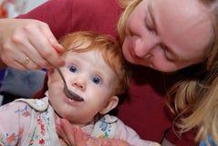 Bebê que alimenta com colher Fotografia de Stock