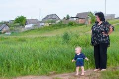 Bebê que anda com sua avó na vila que olha algo interessante imagens de stock royalty free