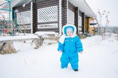 Bebê que anda em uma jarda da neve imagem de stock royalty free