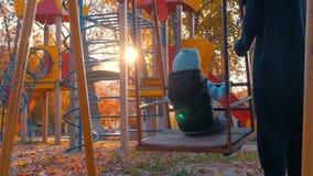 Bebê que balança no campo de jogos das crianças no parque Criança feliz que tem o bom tempo fora filme