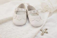 Bebê que batiza as sapatas brancas com o pendente transversal no branco Imagem de Stock