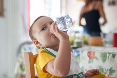 Bebê que bebe de uma garrafa de água durante a refeição imagem de stock