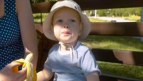 Bebê que come a banana no parque vídeos de arquivo