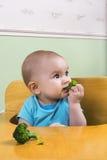 Bebê que come brócolis Fotos de Stock