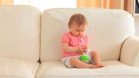 Bebê que come em um sofá
