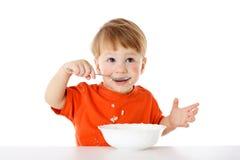 Bebê que come a farinha de aveia imagens de stock royalty free