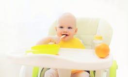 Bebê que come o alimento de colher na casa da tabela Imagem de Stock