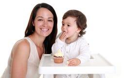 Bebê que come o bolo com mum Fotografia de Stock Royalty Free
