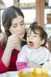 Bebê que come o frasco do comida para bebê Fotografia de Stock Royalty Free
