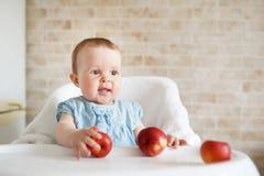 Bebê que come o fruto Menina que morde a maçã amarela que senta-se na cadeira alta branca na cozinha ensolarada Nutrição saudável fotografia de stock royalty free