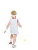 Bebê que corre para a bola de tênis. vista traseira Imagem de Stock
