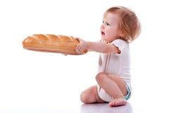 Bebê que dá para fora um naco de pão fotos de stock royalty free