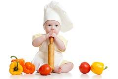 Bebê que desgasta um chapéu do cozinheiro chefe com alimento saudável imagens de stock royalty free